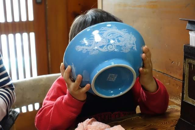 ラーメンスープを飲み干す子供